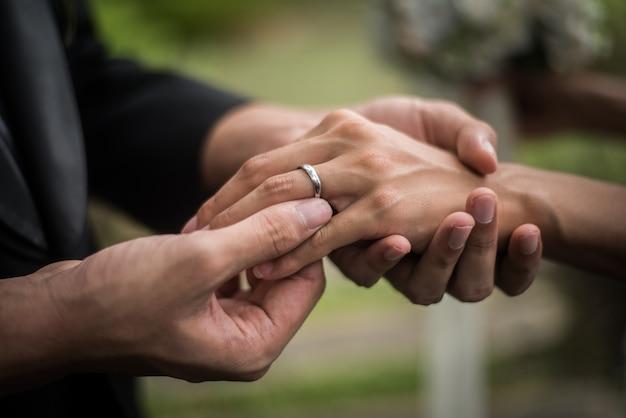 Gros plan du marié porte la bague mariée au jour du mariage. amour, heureux mariage concept. Photo gratuit