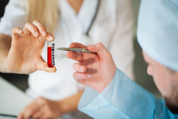 Gros Plan Du Médecin Tenant Des Tubes à Essai Avec Test De Coronavirus. Photo Premium