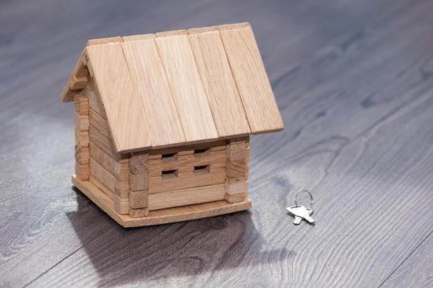 Gros plan du modèle de maison en bois et des clés d'argent sur fond en bois. Photo Premium