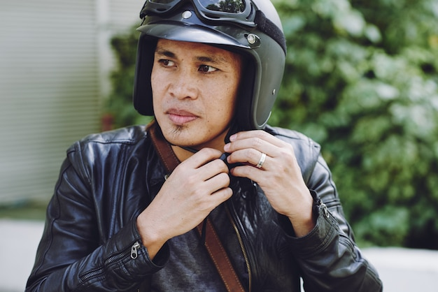 Gros plan du motard mettant son casque Photo gratuit