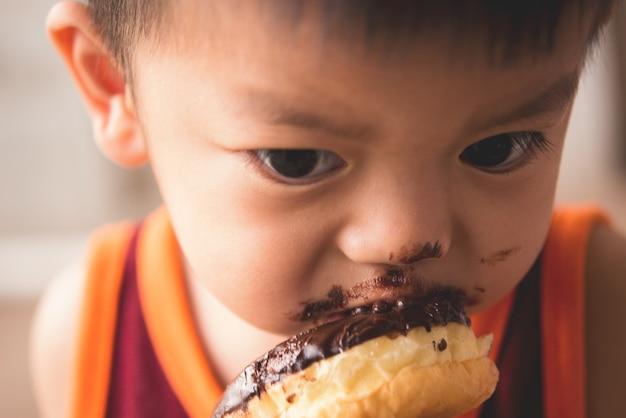 Gros plan du petit garçon affamé eaitng beignet chaud Photo gratuit