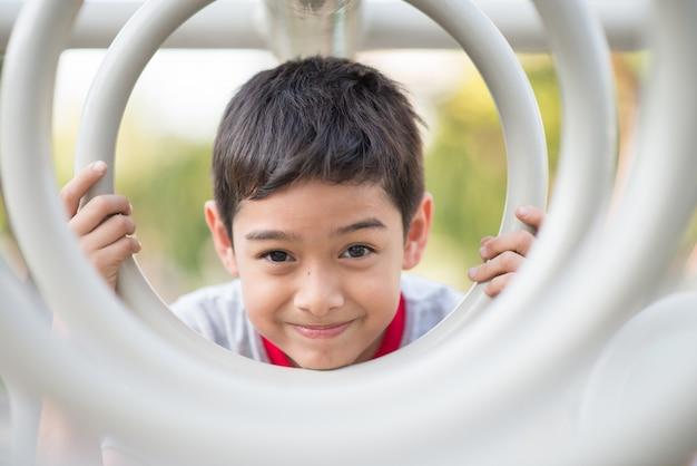 Gros plan du petit visage de garçon accroché sur la barre de cycle au terrain de jeux Photo Premium