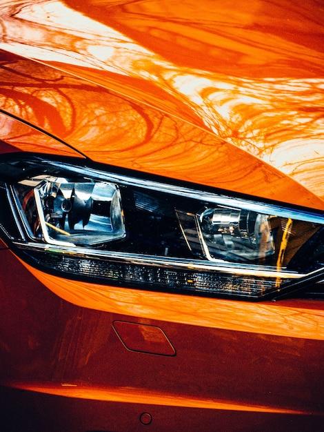 Gros Plan Du Phare Droit D'une Voiture Moderne Orange Photo gratuit