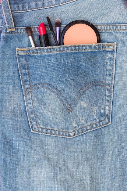 Gros plan du pinceau de maquillage; rouge à lèvres et fard à joues dans la poche de jeans Photo gratuit
