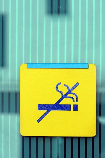 Gros Plan Du Signe Non Fumeur Jaune Sur Mur De Verre Vert Photo Premium