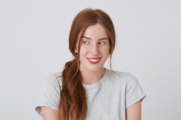 Gros Plan Du Sourire Jolie Jeune Femme Rousse Avec Des Taches De Rousseur Porte Un T-shirt Gris Se Sent Heureux Et Regarde Sur Le Côté Photo gratuit