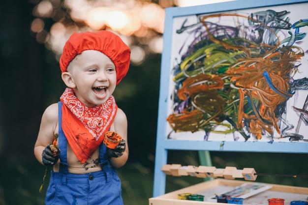 Gros Plan Du Sourire Peintre Garçon. Les Mains Du Garçon De L'artiste, Qui Peint Une Peinture à L'huile Sur La Nature Au Coucher Du Soleil Photo Premium