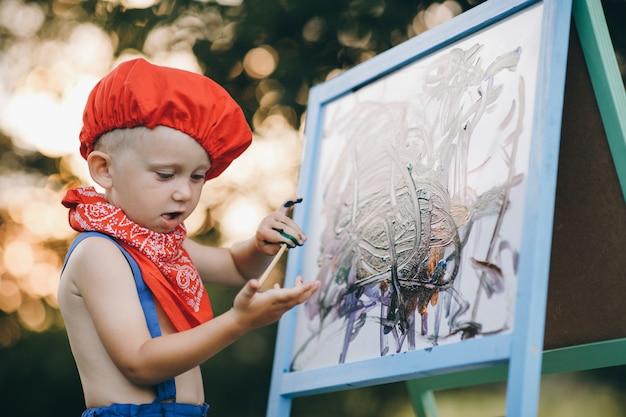 Gros Plan Du Sourire Peintre Homme. Les Mains Du Garçon De L'artiste, Qui Peint Une Peinture à L'huile Sur La Nature Photo Premium