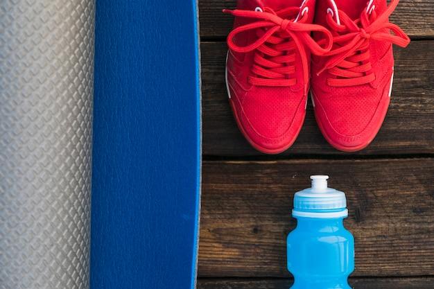 Gros plan du tapis d'exercice enroulé; chaussette et paire de chaussures de sport rouges sur une table en bois Photo gratuit