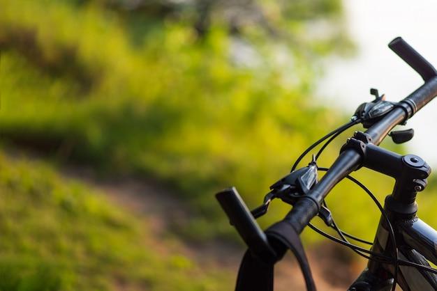 Gros plan du vélo de montagne dans la forêt au coucher du soleil avec fond Photo Premium