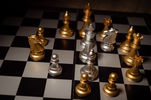 Gros plan des échecs sur le jeu de plateau avec concept de compétition humeur sombre et ton processus Photo Premium