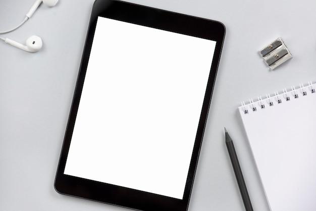 Gros plan des écouteurs; tablette numérique vierge; taille crayon; crayon et bloc-notes en spirale sur fond gris Photo gratuit