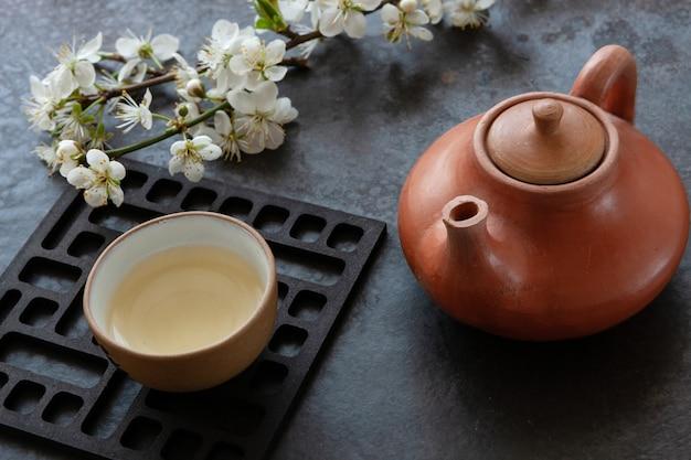 Gros plan de l'ensemble de thé asiatique en céramique avec du thé vert du japon avec des branches de floraison des cerisiers sur la table grise. Photo Premium