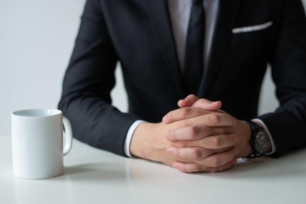 Gros plan d'un entrepreneur réfléchi avec les mains jointes Photo gratuit