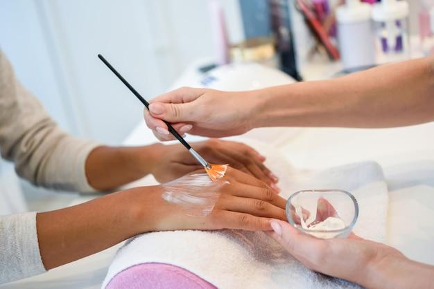Gros plan d'une esthéticienne, appliquer la crème sur la main de la femme à l'aide d'un pinceau. Photo gratuit