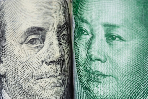 Gros plan face à face avec benjamin franklin et mao tse tung de billets de banque en dollars américains et en yuan chinois. Photo Premium