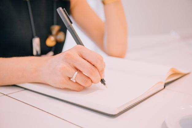 Gros plan, de, femme affaires, écriture, à, stylo, sur, journal Photo gratuit