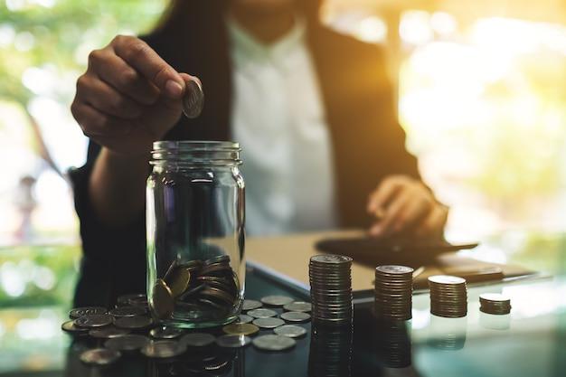 Gros Plan D'une Femme D'affaires Mettant Des Pièces Dans Un Bocal En Verre, Calculant Et Empilant De L'argent Pour économiser Et Concept Financier Photo Premium