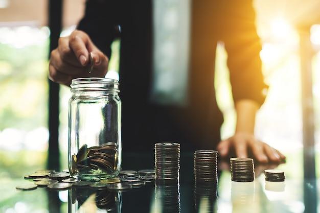 Gros Plan D'une Femme D'affaires Mettant Des Pièces Dans Un Bocal En Verre Avec Des Piles De Pièces Sur La Table Pour économiser De L'argent Et Concept Financier Photo Premium