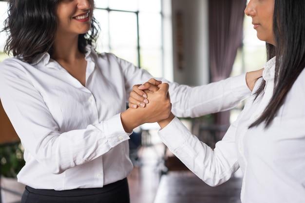 Gros plan d'une femme d'affaires souriant soutenant un collègue au café. Photo gratuit