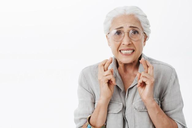 Gros Plan D'une Femme âgée Inquiète Et Nerveuse Dans Des Verres Croiser Les Doigts Et Prier Photo gratuit