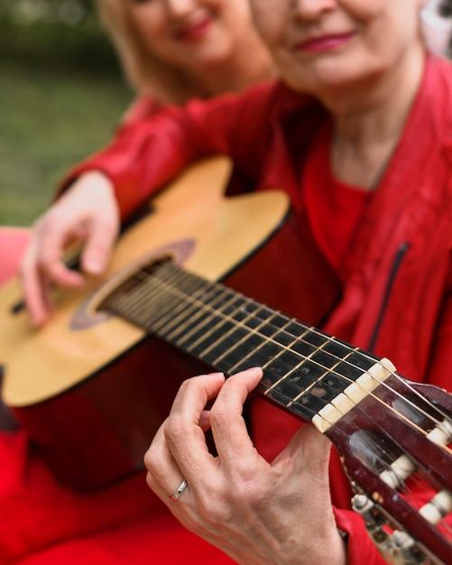 Gros plan femme âgée jouant de la guitare Photo gratuit