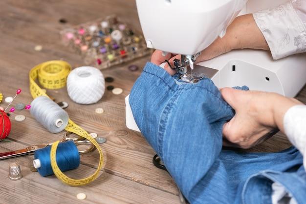 Gros plan, de, femme aînée, couturière, coudre jeans, sur, machine à coudre électrique. Photo Premium