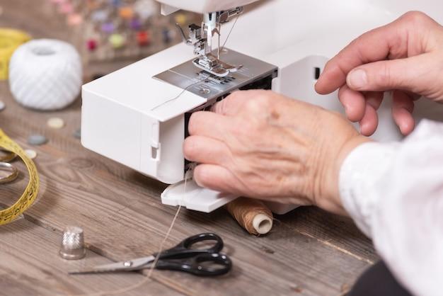 Gros plan, femme aînée, couturière, mains, enlèvement, l'affaire, canette Photo Premium