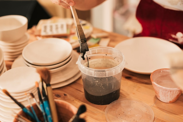 Gros plan, femme, artisan, peinture, plaque céramique, pinceau Photo gratuit
