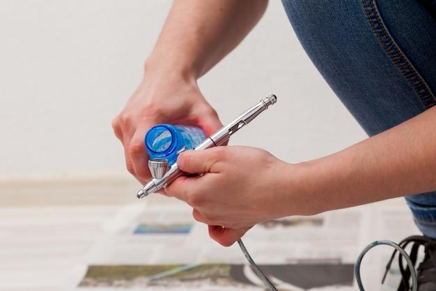 Gros plan d'une femme artiste en jeans nettoie et prépare l'aérographe pour le travail de peinture des murs. Photo Premium