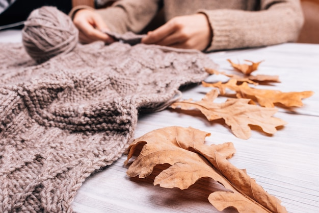 Gros plan d'une femme assise à la table en train de tricoter un pull en laine Photo Premium