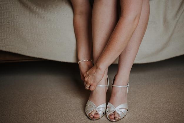 Gros Plan D'une Femme Attachant Ses Chaussures Blanches Photo gratuit