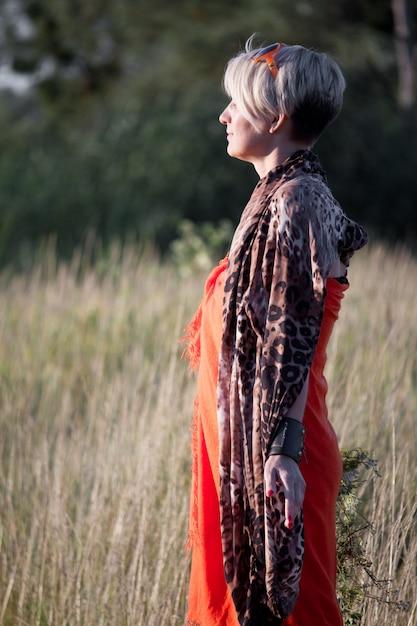 Gros plan d'une femme blonde d'âge moyen debout dans un pré face au soleil et méditant. Photo Premium