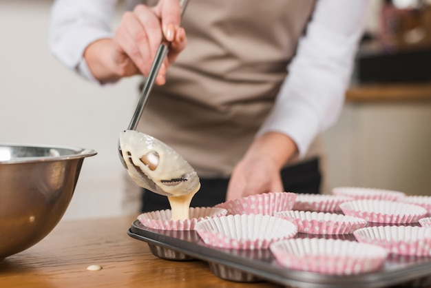 Gros plan, femme, boulanger, verser, pâte mélangée, gâteau, porte-cupcake Photo gratuit