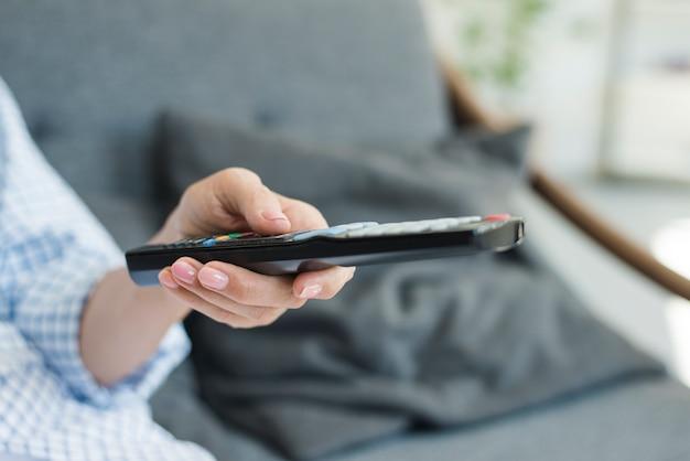 Gros plan, femme, changer canal, à, télécommande Photo gratuit
