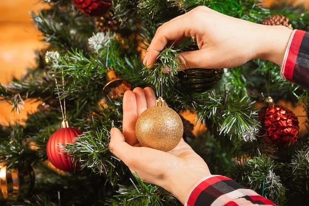 Gros Plan D'une Femme Dans Une Chemise à Carreaux Accroche Une Belle Boule D'or Brillant Sur Un Arbre De Noël Photo Premium