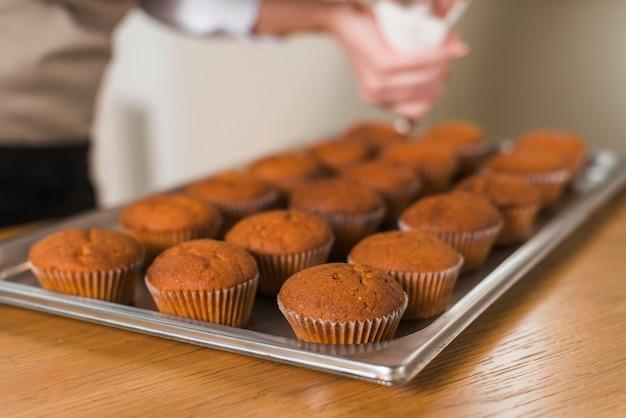 Gros plan, femme, décoration, cuire, frais, muffins, à, crème, sur, plateau Photo gratuit