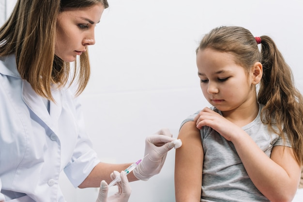 Gros plan, femme, docteur, injection, seringue, bras, patient, contre, fond blanc Photo gratuit