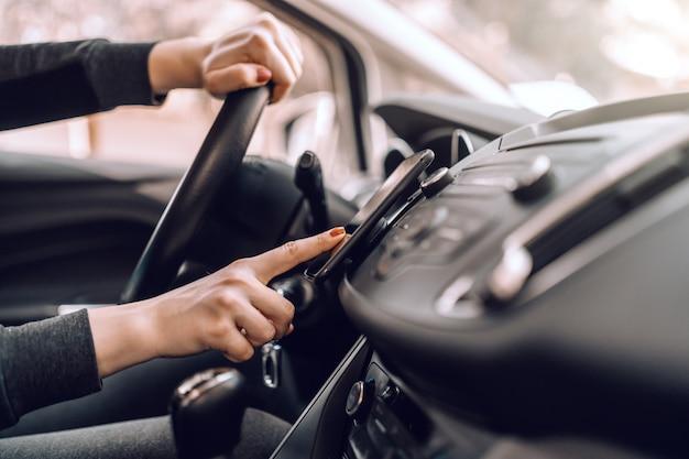 Gros Plan D'une Femme Enceinte Caucasienne, Conduire Une Voiture Et Allumer Le Gps Sur Un Téléphone Intelligent. Photo Premium
