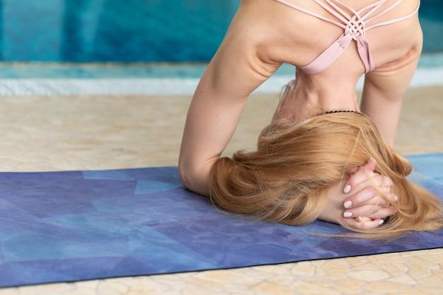 Gros plan de femme faisant des poses de yoga, geste des mains près de la piscine Photo Premium