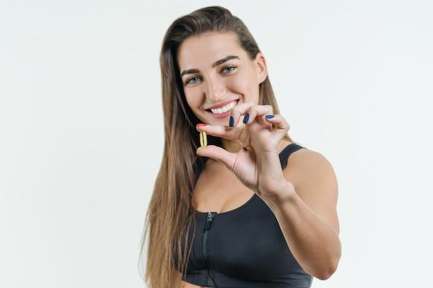 Gros plan d'une femme fitness heureuse prenant des pilules avec de l'huile de foie de morue Photo Premium