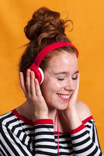 Gros plan femme heureuse, écouter de la musique avec des écouteurs Photo gratuit