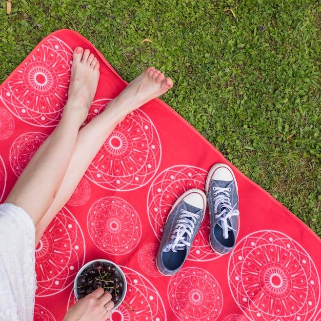Gros plan, de, femme, à, jambe croisée, reposer couverture, tenue, cerises Photo gratuit