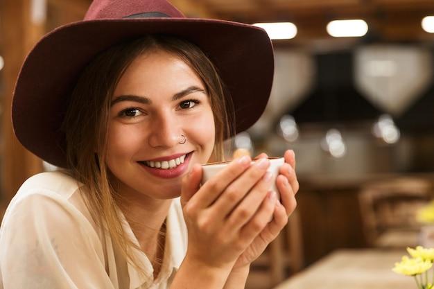 Gros Plan D'une Femme Joyeuse Au Chapeau Assis à La Table Du Café Photo Premium