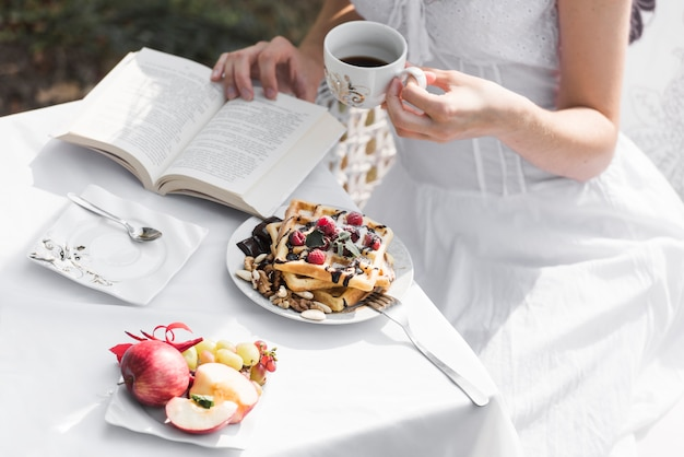 Gros Plan D'une Femme Lisant Un Livre Tout En Prenant Son Petit Déjeuner Photo gratuit