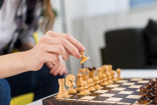 Gros plan, femme, main, jouer, échiquier bois Photo gratuit