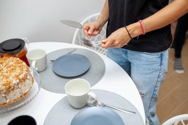 Gros Plan, Femme, Mains, Tenue, Gâteau, Spatule, Fourchette Sur La Table Est Un Gâteau, Des Assiettes Et Des Tasses. Fête Du Thé Maison Photo Premium