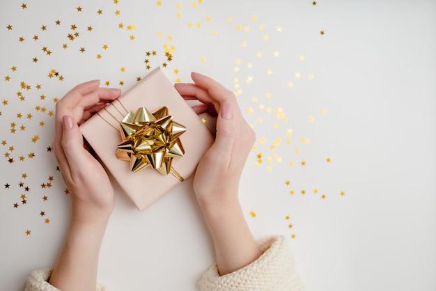 Gros Plan, Femme, Mains, Tenue, Présent Fond De Noël Festif Avec Fond. Vue Horizontale Supérieure Photo Premium