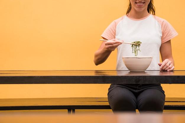 Gros plan, femme, manger, algues vertes, baguettes, table bois, contre, toile de fond jaune Photo gratuit