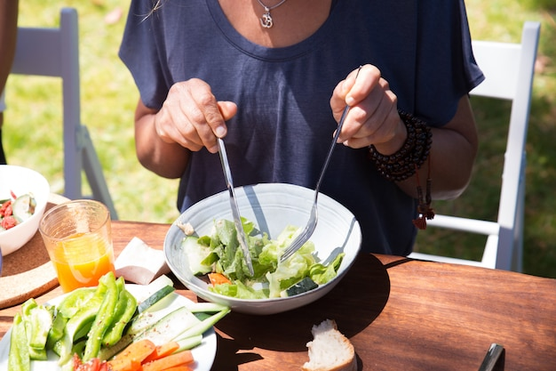 Gros plan, femme, manger, salade, table, dehors Photo gratuit